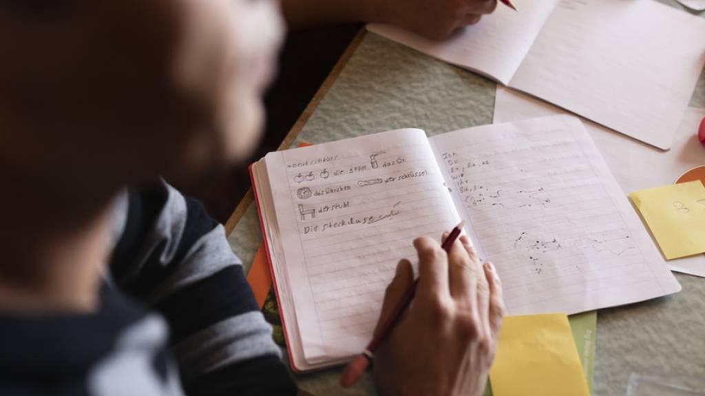 Ein Flüchtling in einem Deutschkurs. Laut einem Bericht zahlen sich solche Integrationsmassnahmen aus. (Themenbild)