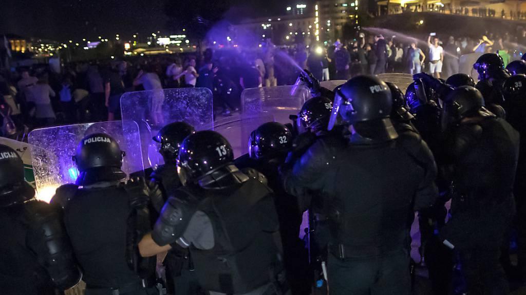 Die Bereitschaftspolizei setzt Tränengas während einer regierungskritischen Kundgebung vor dem Parlamentspalast ein. Die Demonstranten bekunden ihren Unmut über die Corona-Beschränkungen. Foto: Mindaugas Kulbis/AP/dpa