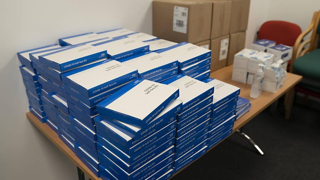ARCHIV - Testkits für einen Corona-Selbsttest liegen gestapelt auf einem Tisch, in einer Schule bei Manchester. Foto: Jon Super/AP/dpa