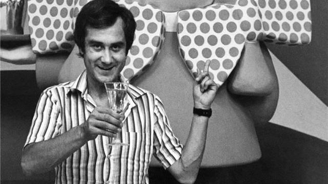 Der Schweizer Teleboy-Moderator Kurt Felix posiert mit einem Champagnerglas vor dem Telegirl-Maskottchen. Foto: Keystone