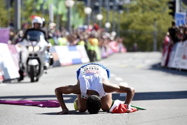 Der Sieger küsst den Boden.