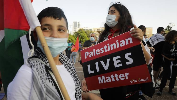 Eine Demonstrantin hält ein Schild mit einer Protestparole während eines Protests gegen die Pläne Israels, Teile des Westjordanlandes zu annektieren. Foto: Sebastian Scheiner/AP/dpa