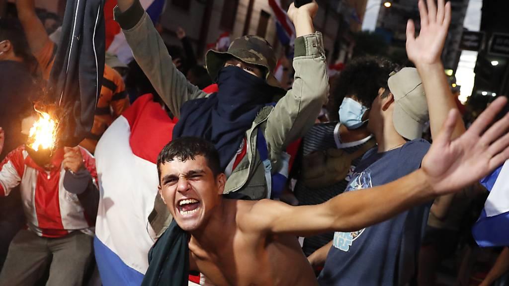 Jugendliche protestieren gegen die Regierung von Präsident Mario Abdo Benitez wegen des Mangels an Medikamenten für Covid-19-Patienten in Krankenhäusern und die geringe Verfügbarkeit des Impfstoffs. Bei den Protesten ist es in Paraguay zu schweren Krawallen gekommen. Foto: Jorge Saenz/AP/dpa