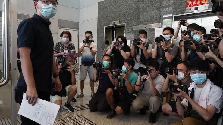 Der pro-demokratische Aktivist Joshua Wong (l) zeigt Journalisten die Nominierungsunterlagen, während er seine Kandidatur für die im September in Hongkong stattfindenden Wahlen zum Legislativrat einreicht. Foto: Vincent Yu/AP/dpa