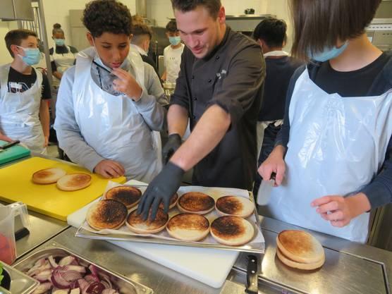 Hoteldirektor Philipp Laube (Mitte) bearbeitet die etwas zu dunkel geratenen Burgerbuns.