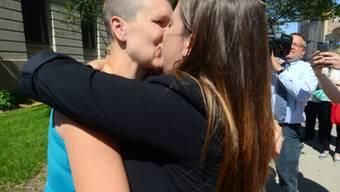 Lesbisches Paar küsst sich nach der Hochzeit (Symbolbild)