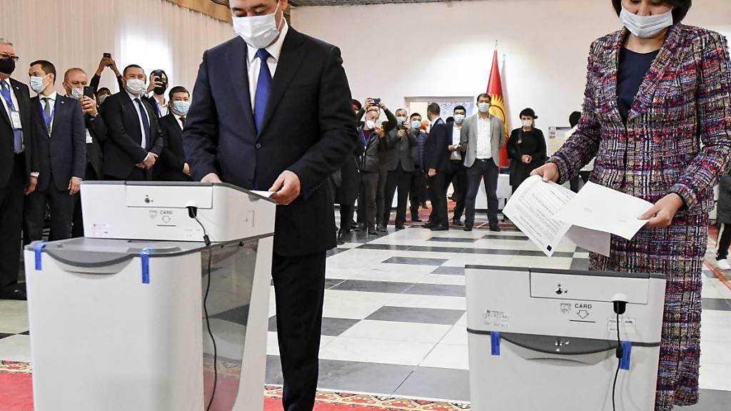 Sadyr Schaparow (l), Präsident von Kirgisistan, und seine Frau Aigul Asanbaeva geben während des Referendums ihre Stimmen in einem Wahllokal ab. Foto: Vladimir Voronin/AP/dpa