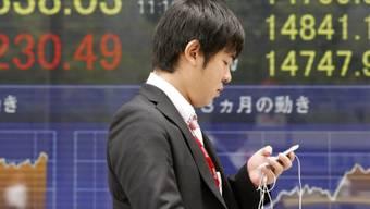 Mann vor einer Börsenanzeige in Tokio