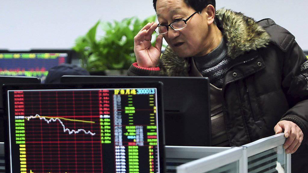 Wo bloss bleibt das Wachstum der Volkswirtschaft: Chinesischer Investor schaut sich Börsenkurse an. (Symbolbild)