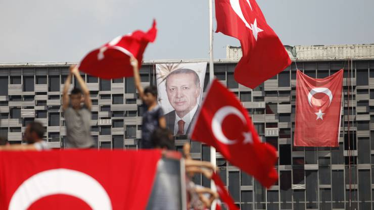 Die Bevölkerung steht hinter Präsident Erdogan An einem Gebäude am Taksim-Platz in Istanbul hängt sein Porträt, davor schwenken Anhänger türkische Flaggen.