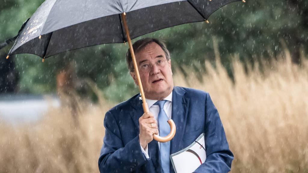 ARCHIV - Armin Laschet, CDU-Bundesvorsitzender und Ministerpräsident von Nordrhein-Westfalen, kommt unterm Regenschirm zu Sondierungsgesprächen zwischen der CDU und Bündnis 90/Die Grünen nach der Bundestagswahl. Foto: Michael Kappeler/dpa