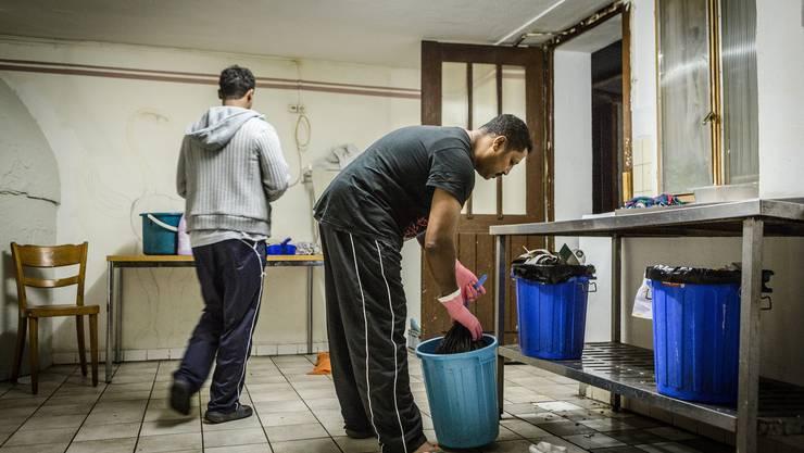 Vier Asylbewerber reinigen die Räume im Erdgeschoss und leeren die Aschenbecher.