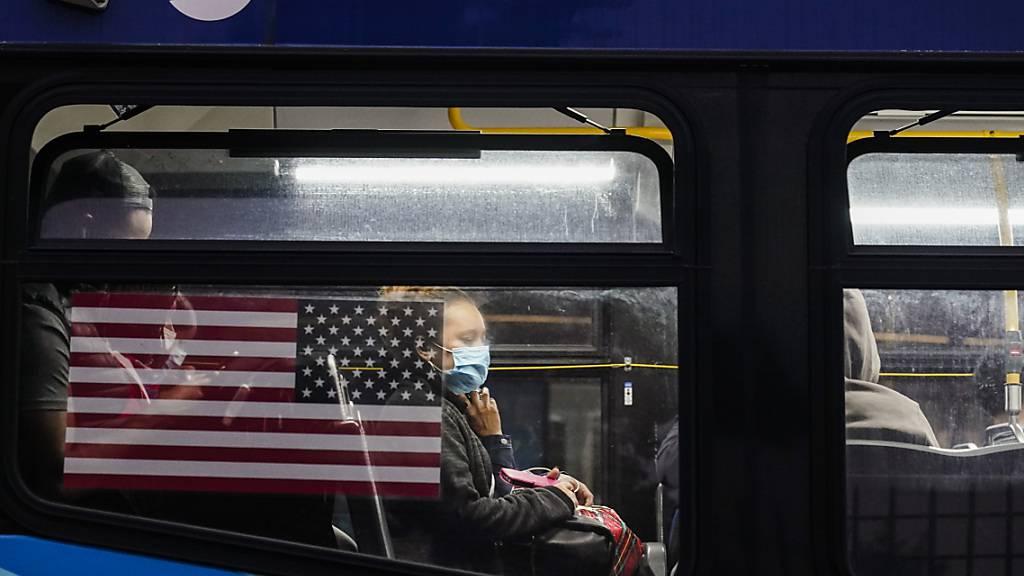 ARCHIV - Eine Frau trägt aufgrund der Corona-Pandemie einen Mund-Nasen-Schutz, während sie in einem Bus in New York sitzt. Foto: Frank Franklin Ii/AP/dpa