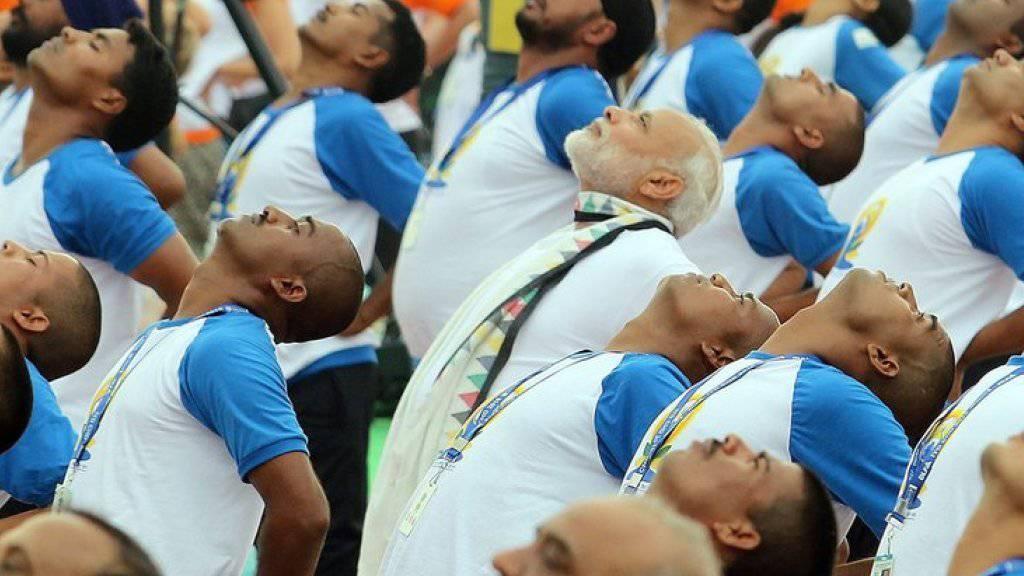 Der zweite Weltyogatag in Indien mobilisiert hunderttausende Menschen. Auch der indische Premierminister Narendra Modi (in Weiss) lässt sich die Yogastunde nicht entgehen.