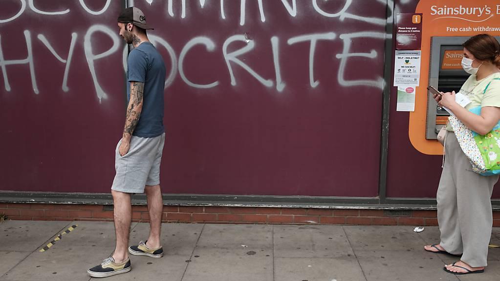 Ein Mann und eine Frau mit Mundschutz gehen an einem Graffiti vorbei, das an die Wand eines Supermarkts in der Nähe des Hauses von Regierungsberater Cummings gesprüht wurde. Das Graffiti mit der Aufschrift «Scummings Hypocrite» (Heuchler)  kritisiert Cummings, der trotz des Lockdowns mehr als 400 Kilometer zu seinen Eltern gereist ist, als er an Covid-19-Symptomen litt.