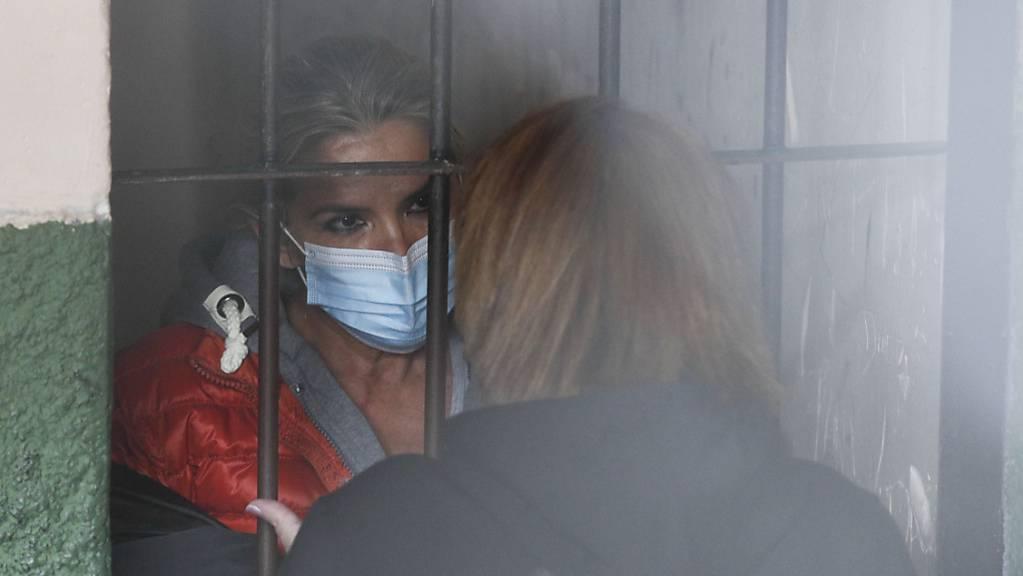 Auf einer Polizeistation im Gefängnis in la Paz spricht Jeanine Áñez, Boliviens ehemalige Interimspräsidentin, durch Gitterstäbe hindurch mit einer Frau.