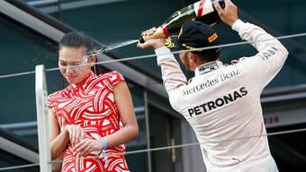 Lewis Hamilton verpasst der F1-Hostess eine Champagner-Dusche.
