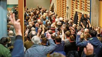 Bürgerinnen und Bürger stimmen bei einer Gemeindeversammlung in Vals – wo auch Ausländer teilnehmen dürfen – per Handaufhalten ab.
