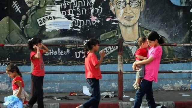 Palästinenser spazieren vor einem Wandbild des seit 2006 inhaftierten Gilad Schalit (Archiv)