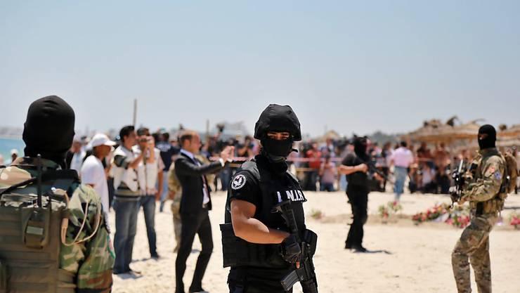 Polizisten am Strand von Sousse während einer Gedenkveranstaltung für die Opfer des Attentats (Archiv)
