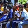 Menschen sitzen, ohne Abstand voneinander zu halten, in einer Schlange vor dem Postamt, um soziale Zuschusszahlungen zu erhalten. Foto: Theo Jeptha/AP/dpa