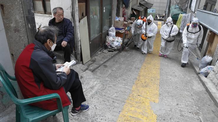 Arbeiter sprayen Desinfektionsmittel in den Strassen von Seoul in Südkorea.
