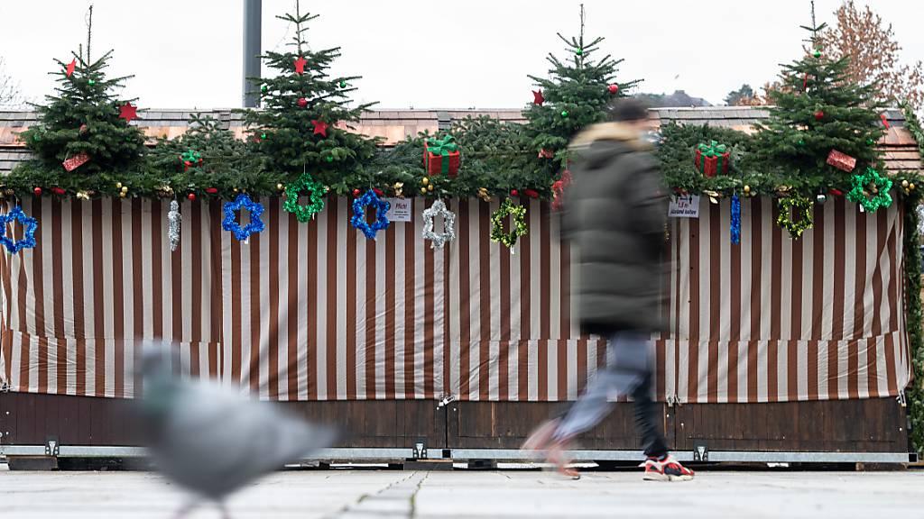 Eine Taube und ein Mann, der einen Mund-Nasenschutz trägt, gehen an einem geschlossenen Verkaufsstand vorbei, der eigentlich für den Weihnachtsmarkt bestimmt war. Foto: Sebastian Gollnow/dpa