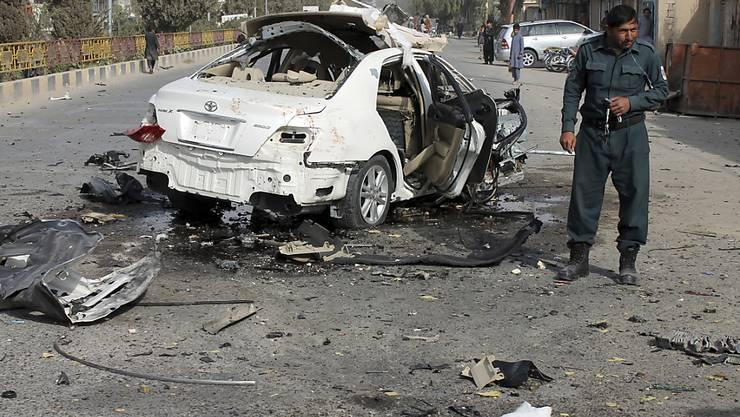 Ein Polizist untersucht ein beschädigtes Auto nach einem Bombenanschlag in der südafghanischen Provinz Helmand. Eine Bombe am Fahrzeug eines Journalisten explodierte am Donnerstag und tötete ihn. Mindestens zwei weitere Menschen, darunter der Bruder des Opfers, seien verwundet worden. Foto: Abdul Khaliq/AP/dpa