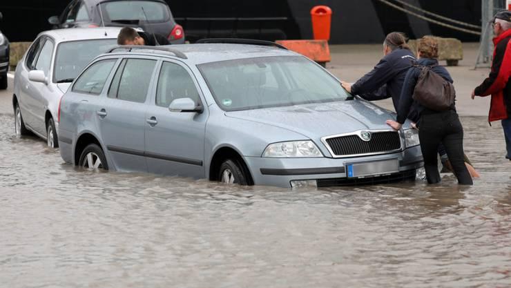 """Auf einem Parkplatz im Stadthafen von Rostock (Mecklenburg-Vorpommern) stehen am Donnerstag nach stundenlangem Dauerregen Fahrzeuge im Wasser. Sturmtief """"Xavier"""" fegte am Donnerstag über Deutschland."""