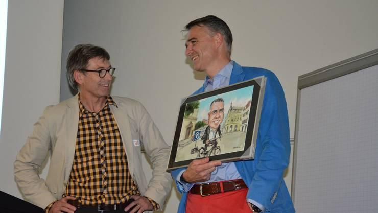 Laudator Marius Studer (links) und scheidender Präsident Fabian Aebi mit dem Geschenk, einem gemalten Bild.