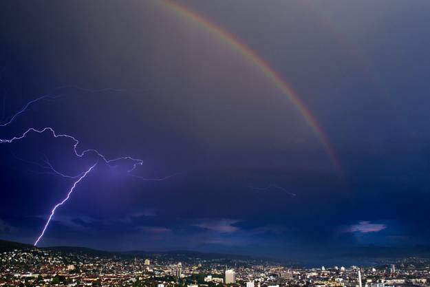 Ein Gewitter mit Blitz und Regenbogen zieht über Zürich