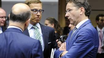 EU-Währungskommissar Pierre Moscovici (links) zusammen mit dem finnischen Finanzminister Alexander Stubb (mitte) und dem Eurogruppen-Chef Jeroen Dijsselbloem (rechts) in Brüssel.