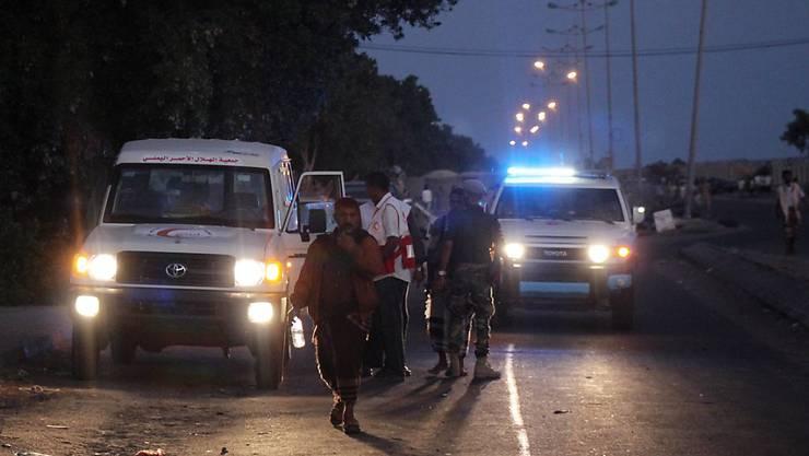 Vertreter der Hilfsorganisation Roter Halbmond und Sicherheitsleute am Ort des Anschlags in Aden.