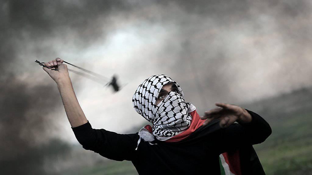 Ein Palästinenser greift israelische Sicherheitskräfte mit einer Steinschleuder an: Bei mehreren Zwischenfällen und Zusammenstössen im Nahen Osten gab es am Samstag mehrere Verletzte. (Archivbild)