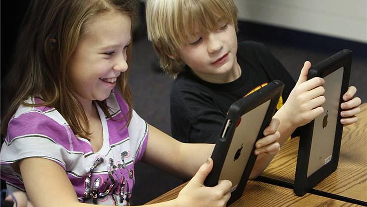 Der iPad als Schulbuch, Heft und Tafel: Schüler während des Unterrichts mit dem Tablet-PC von Apple.