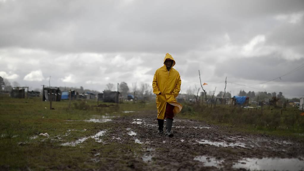 dpatopbilder - Ein Mann geht durch eine informelle Siedlung in Buenos Aires. Foto: Natacha Pisarenko/AP/dpa