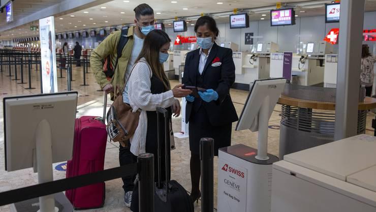 Passagiere am Swiss Check-in Schalter am Flughafen Genf.