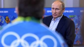 Russlands Präsident Vladimir Putin spricht mit jugendlichen Helfern der Olympiade in Sotchi.