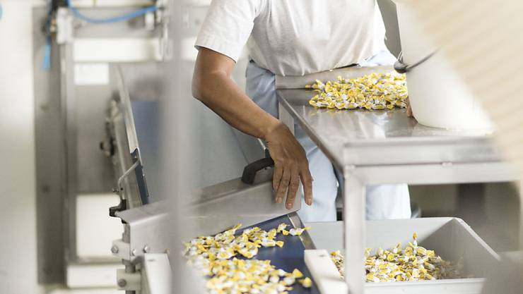 """Eine Mitarbeiterin sortiert in der Ricola-Fabrik in Laufen die """"Däfeli"""" des Baselbieter Süsswaren-Produzenten (Archivbild)."""