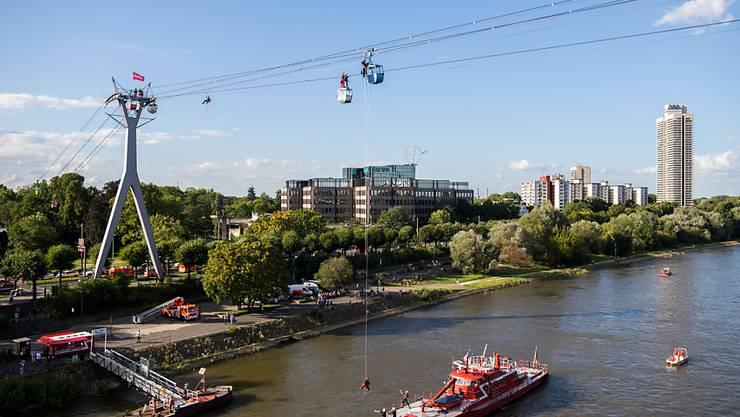 In Köln hat die Feuerwehr Dutzende Gäste einer Seilbahn aus einer prekären Lage befreien müssen. Hier wird ein Mann über dem Rhein aus einer Gondel abgeseilt.