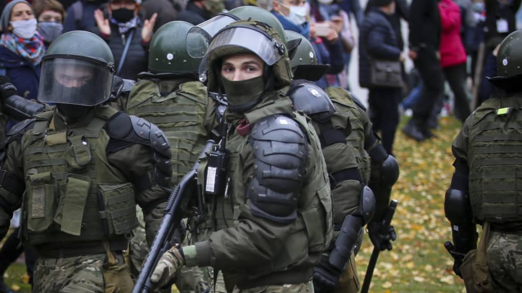 Polizisten blockieren eine Straße vor Demonstranten während einer Kundgebung der belarussischen Opposition. Trotz neuer Gewaltandrohung haben Zehntausende Menschen gegen den Langzeitpräsidenten Lukaschenko demonstriert. Foto: Uncredited/AP/dpa