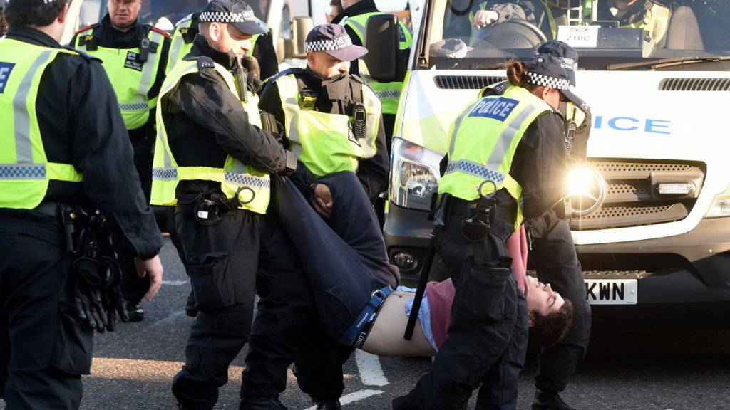 Ein Demonstrant wird von der Polizei von der Lambeth Bridge weggetragen.