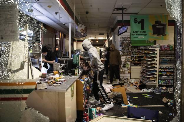 Protestierende in einem zerstörten 7-Eleven-Laden in Chicago.