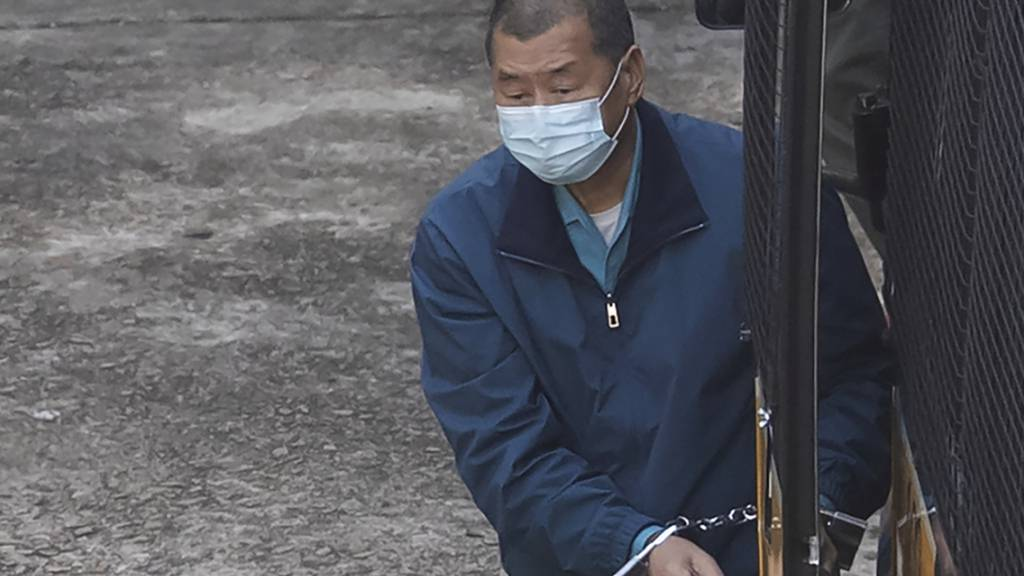 dpatopbilder - Jimmy Lai, Medienunternehmer, Herausgeber der Hongkonger Zeitung «Apple Daily» und pro-demokratischer Aktivist, wird von Beamten des Strafvollzugs in Handschellen aus einem Gefangenentransporter heraus ins Gefängnis begleitet. Foto: Kin Cheung/AP/dpa