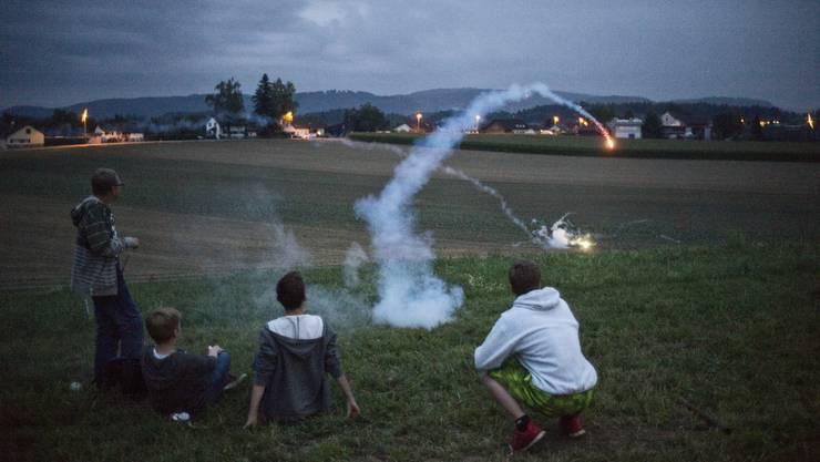 Kurz vor dem Fackel und Lampionumzug lassen einige junge Dorfbewohner in Birrhard ihre Raketen ab