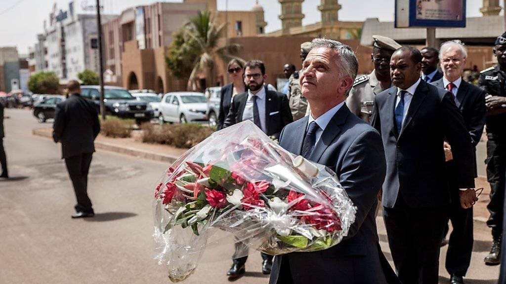 Zum Gedenken an die Opfer der Anschläge von Ouagadougou im Januar bringt Bundesrat Didier Burkhalter Blumen vor das Café, das damals angegriffen wurde.