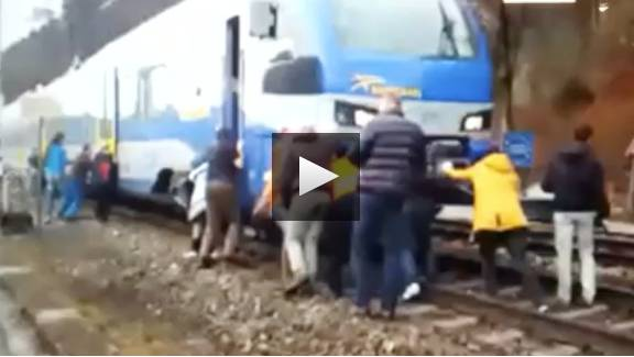 Passagiere schieben stehengebliebenen Zug.