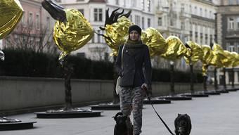 Eine Passantin vor den verhüllten Skulpturen in Prag. Ai Weiwei will mit der Aktion an das Schicksal von Flüchtlingen erinnern.