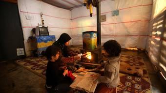 Eine Mutter feuert einen Ofen an. Reiche Ölstaaten wollen keine Flüchtlinge aufnehmen. (Symbolbild)