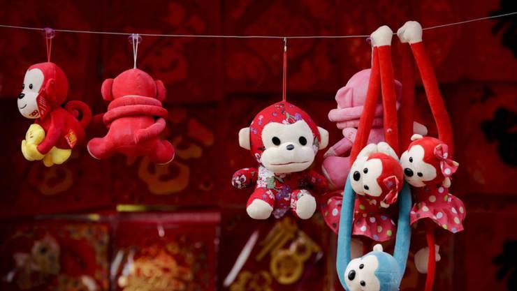 """Affenfiguren aus Plüsch auf einem chinesischen Markt. Schweizer Manager im """"Reich der Mitte"""" bleiben optimistisch für das Jahr des Affen."""